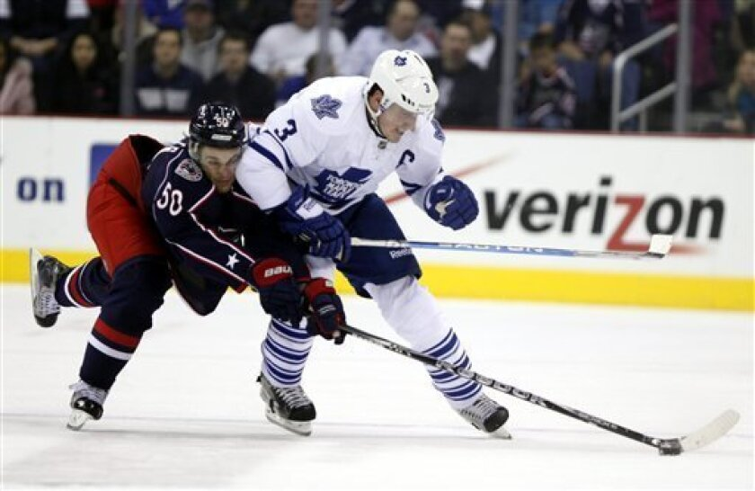 Columbus Blue Jackets' Antoine Vernette (50) runs into Toronto Maple Leafs' Dion Phaneuf (3) while chasing after the puck during the first period of an NHL hockey game, Thursday, Nov 3, 2011, in Columbus, Ohio. (AP Photo/Terry Gilliam)
