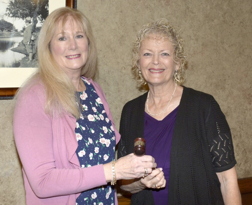 Outgoing La Providencia Guild President Sue Meckley, right, turns the presidential gavel over to Nancy Wiggins who will lead the organization through 2021.