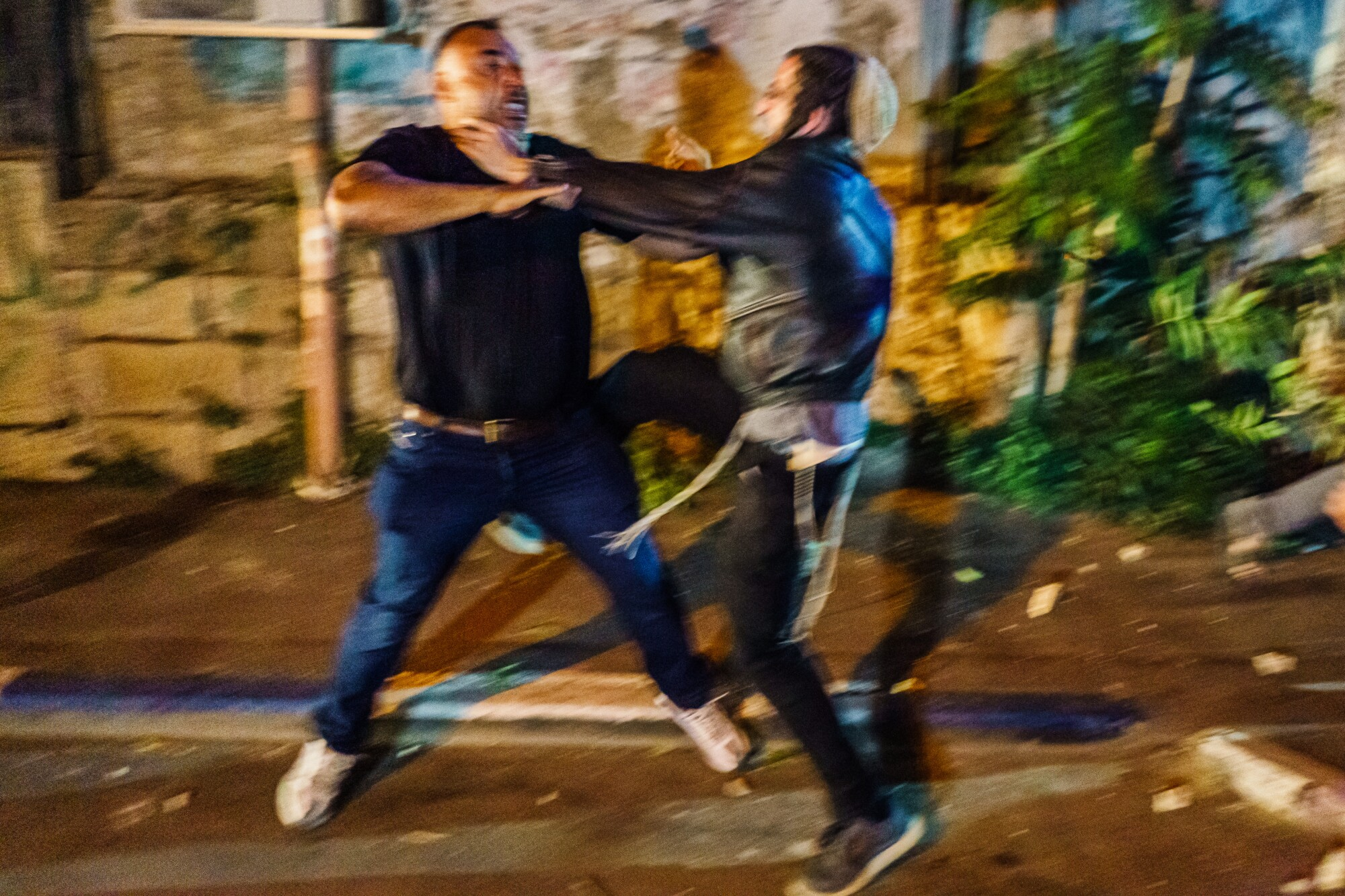 A man puts his hands on another man's neck during a street fight