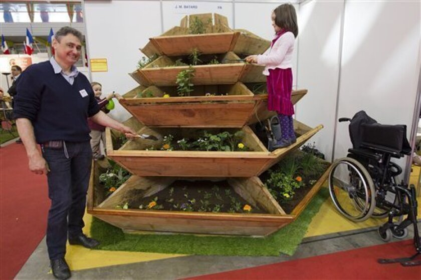 French Jean Marc Batard presents his invention a vertical garden which allows elderly people to garden. It can also be used by people who love gardening but cannot bend down at the 39th International Exhibition of Inventions, New Techniques and Products, in Geneva, Switzerland, Wednesday, April 6, 2011. 765 exhibitors from 45 countries are presenting around 1000 products at the 39th International Exhibition of Inventions, which runs from April 6-10. (AP Photo/Keystone, Salvatore Di Nolfi)
