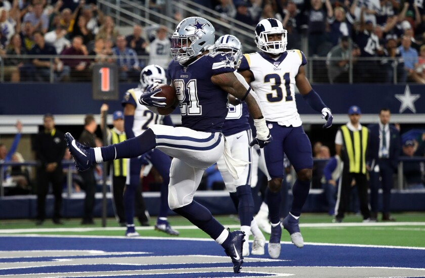 Dallas Cowboys running back Ezekiel Elliott scores a touchdown during the second quarter of Sunday's win over the Rams.