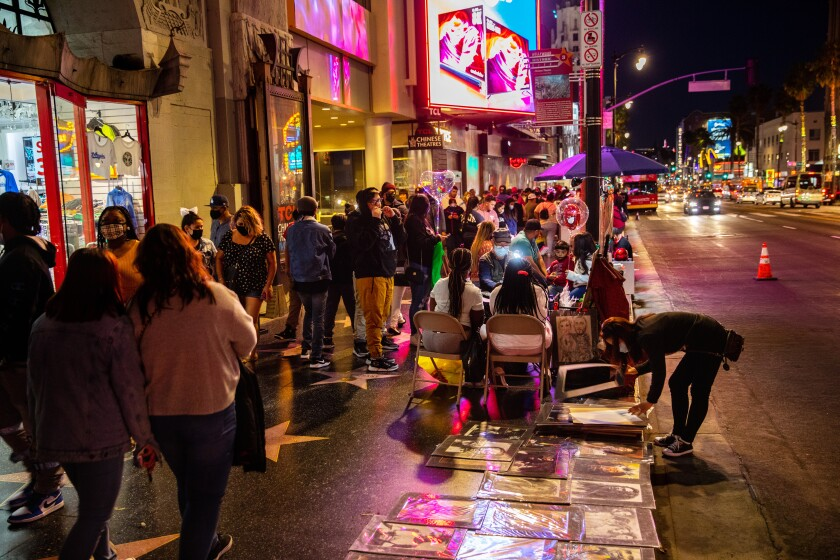 """Hollywood, CA - March 20: The scene along Hollywood Blvd, in the heart of Hollywood, CA, as COVID-19 restrictions are loosened and people filled the sidewalks Saturday, March 20, 2021. This is one year and one day, after California Gov. Gavin Newsom issued a stay at home order, """"to protect the health and well-being of all Californians and to establish consistency across the state in order to slow the spread of COVID-19."""" As of March 19, 2021, 57,510 people died from the coronavirus, with more than 3million positive cases. (Jay L. Clendenin / Los Angeles Times)"""