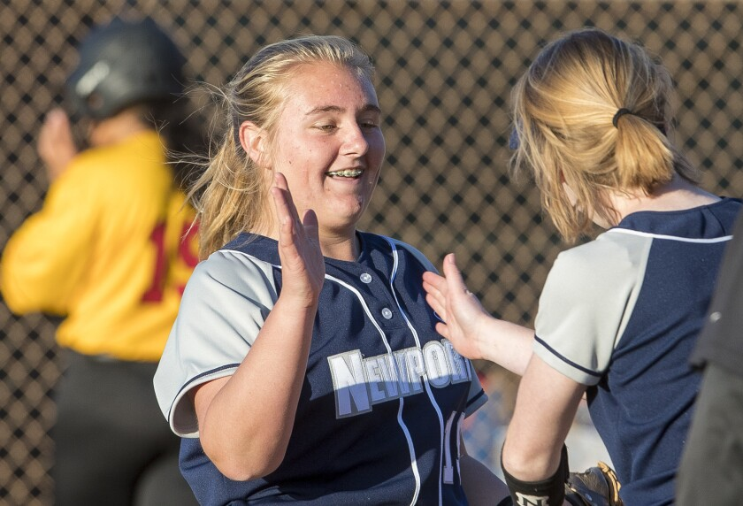Newport Harbor's Clare Austin gets a high five from teammate Lily Larkins after closing out the game against Estancia on Wednesday, February 28.