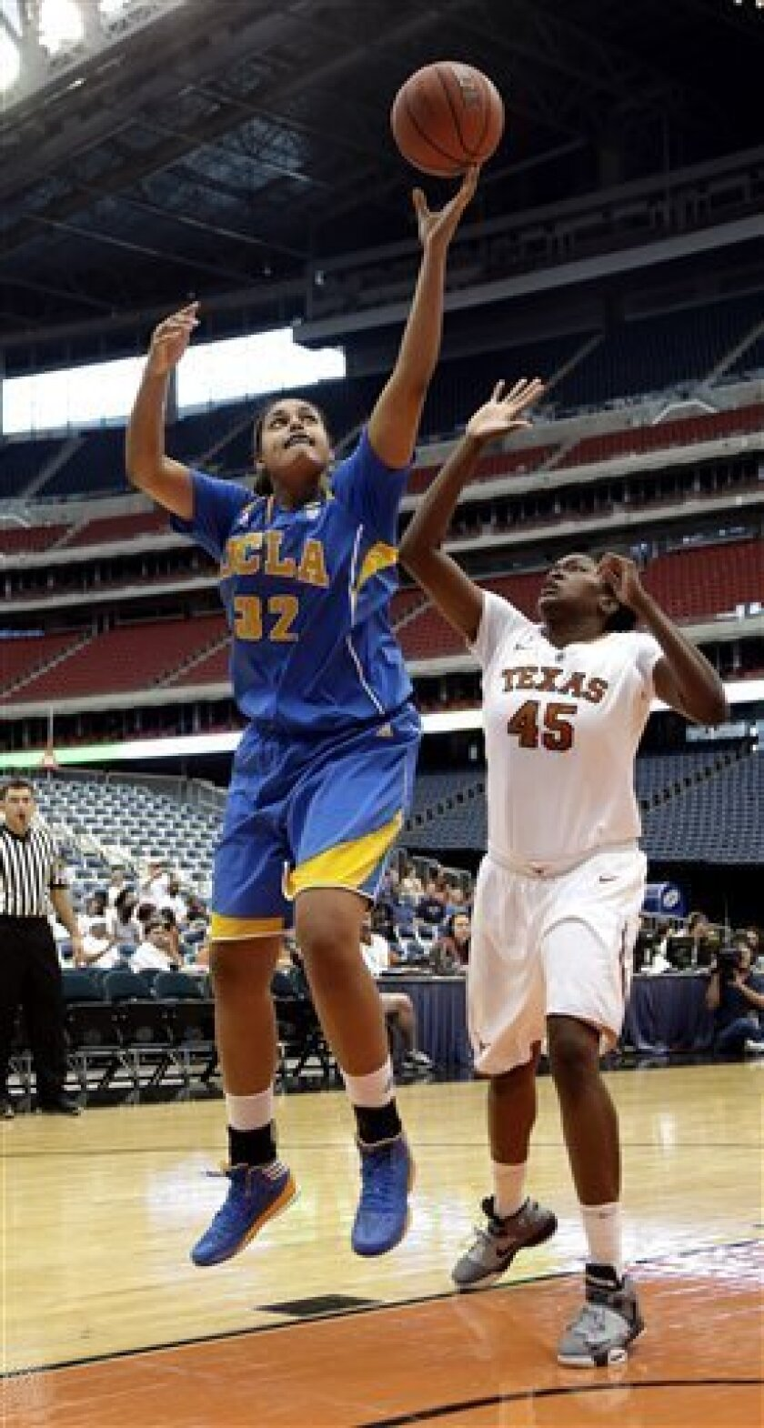 UCLA's Alyssia Brewer (32) shoots as Texas' Cokie Reed (45) defends during the second half of an NCAA college basketball game at Reliant Stadium Saturday, Dec. 8, 2012, in Houston. UCLA beat Texas 62-42. (AP Photo/David J. Phillip)