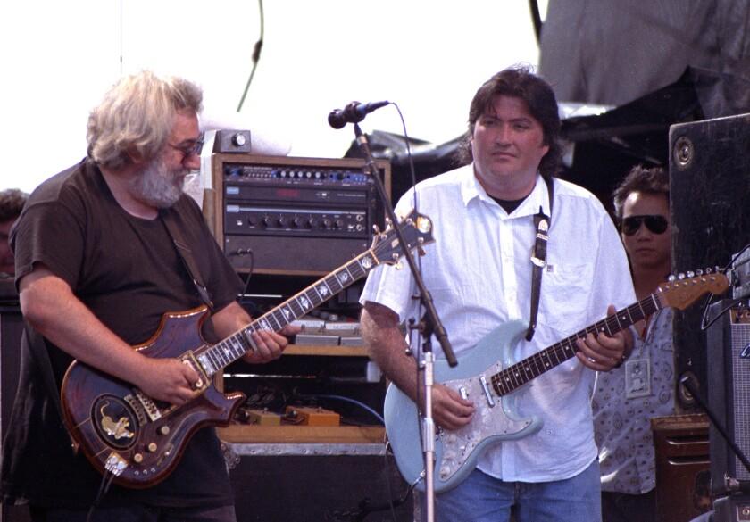Jerry Garcia and David Hidalgo play guitars as they perform at Laguna Seca Raceway.