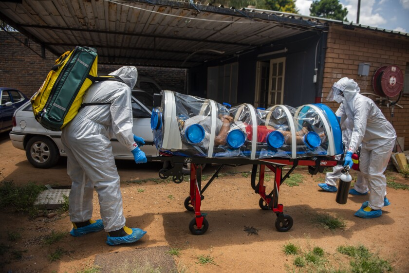 Members of the Tshwane Special Infectious Unit on COVID-19 wearing personal protective equipment pick up a patient.