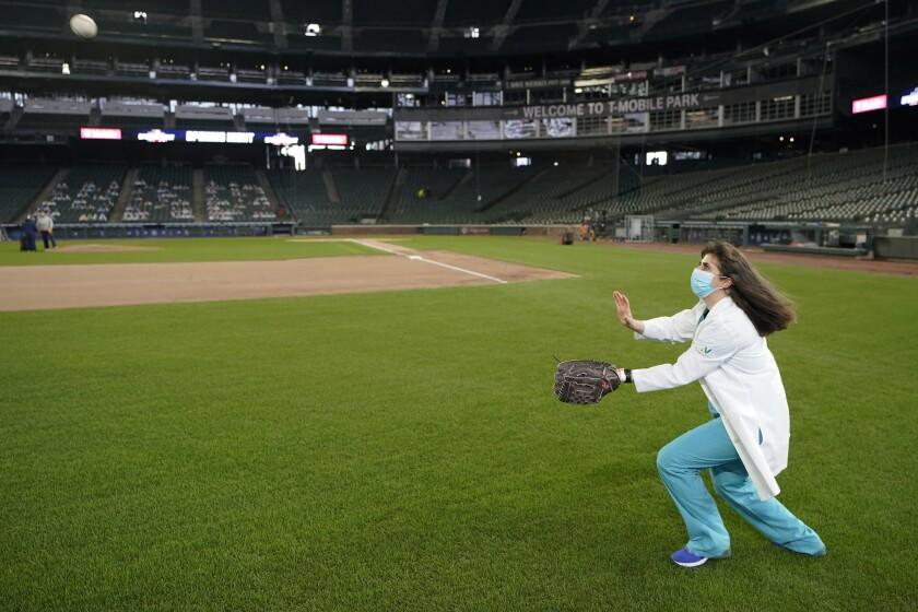 La doctora Amy Portacci, una osteópata, trata de atrapar una pelota al jugar con un colega