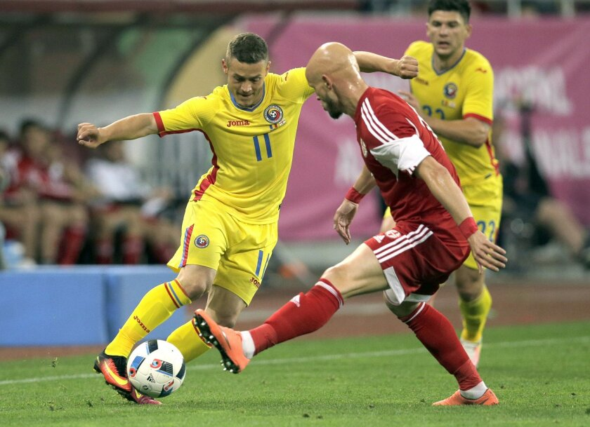 Romania's Gabriel Torje, left, vies for the ball with Georgia's Zourab Tsiskaridze, right, during the international friendly soccer match between Romania and Georgia on the National Arena stadium, in Bucharest, Romania, on Friday, June 3, 2016. (AP Photo/Vadim Ghirda)