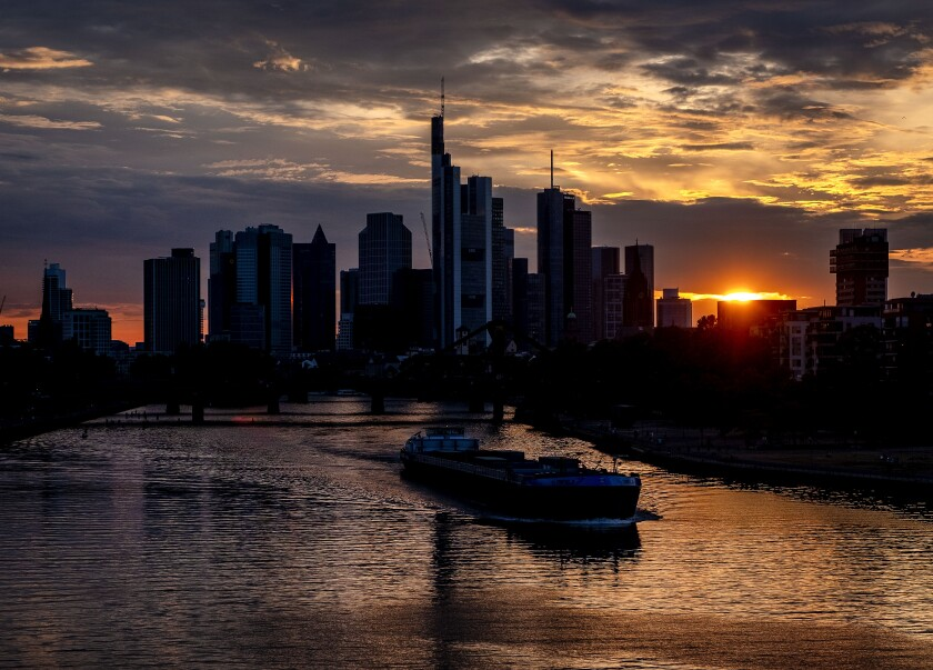 A cargo vessel cruises on the river Main in Frankfurt, Germany