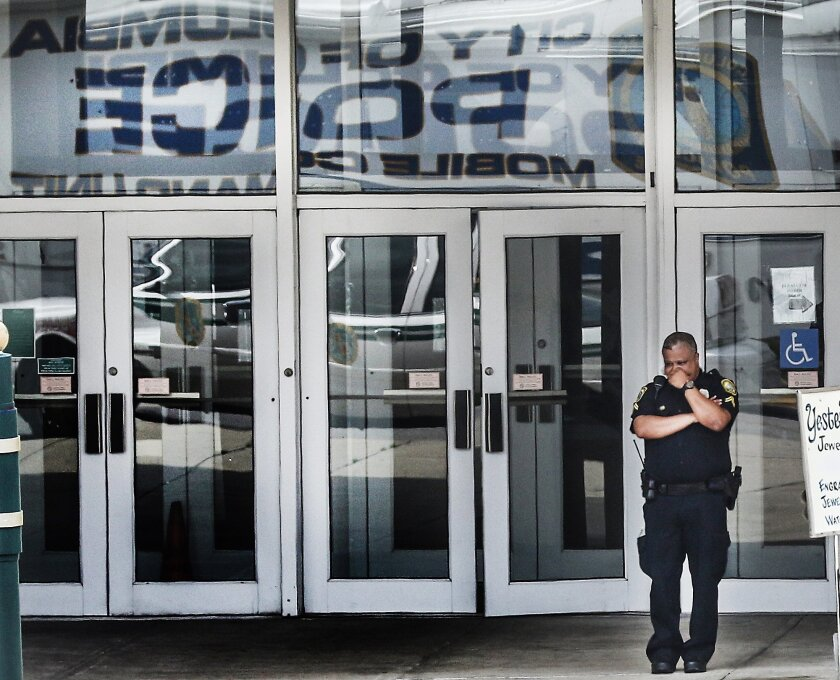 A Columbia police officer walks near the scene where a Forest Acres police officer was fatally shot in the Richland Mall Wednesday, Sept. 30, 2015, in Forest Acres, S.C. Police say a suspect is in custody. (Matt Walsh/The State via AP)