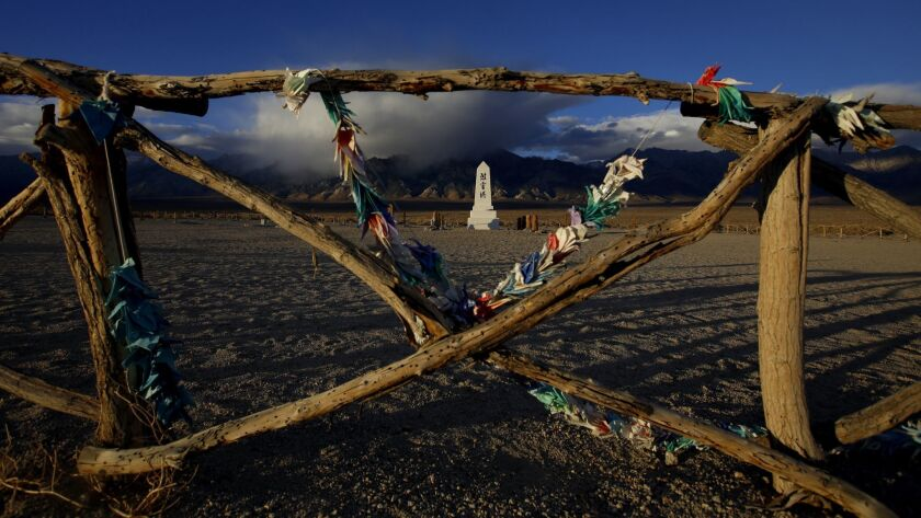 INDEPENDENT, CA - NOVEMBER 19, 2016: Origami cranes left near the monument sway in the strong wind a
