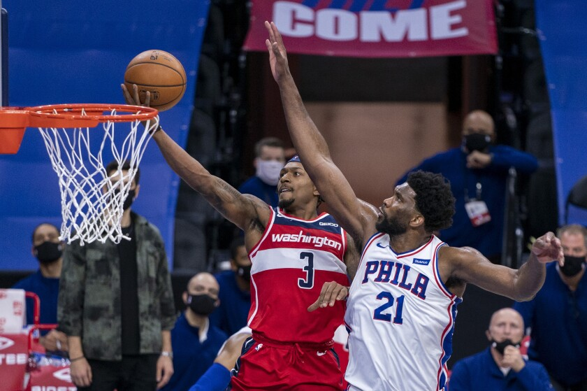 Washington Wizards guard Bradley Beal, left, goes up for the shot against Philadelphia 76ers center Joel Embiid, right, during the second half of an NBA basketball game, Wednesday, Jan. 6, 2021, in Philadelphia. The 76ers won 141-136. (AP Photo/Chris Szagola)