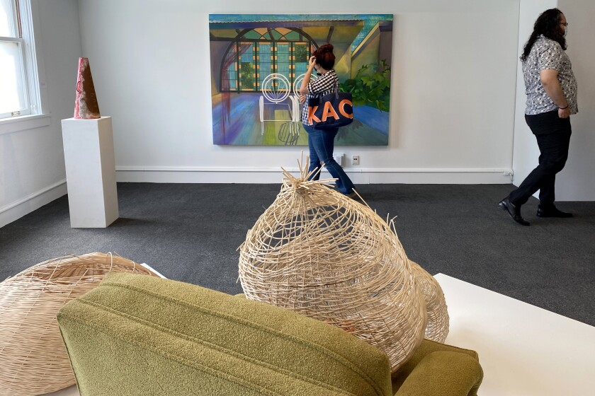 """During the gallery reception, visitors view art displayed at the """"CSUF MFA @Muzeo"""" exhibit."""