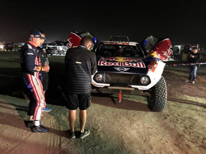 El piloto español Carlos Sainz (i) a su llegada a la medianoche al campamento tras pasarse unas 16 horas en el coche. EFE