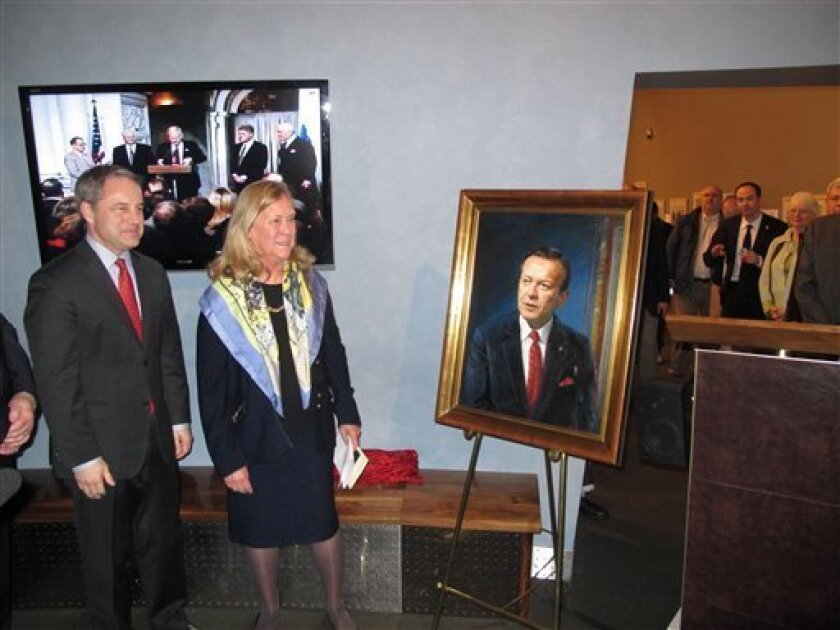 """Gov. Sean Parnell and Catherine Stevens stand next to a portrait of the late-U.S. Sen. Ted Stevens at the Alaska State Museum on Friday, Feb. 3, 2012, in Juneau, Alaska. The crowd overflowed from the exhibit hall, and a video honoring Stevens, made for the occasion, played in the background. Catherine Stevens, Stevens' widow, said the family wanted to offer thanks """"for bringing him home to the state."""" (AP Photo/Becky Bohrer)"""