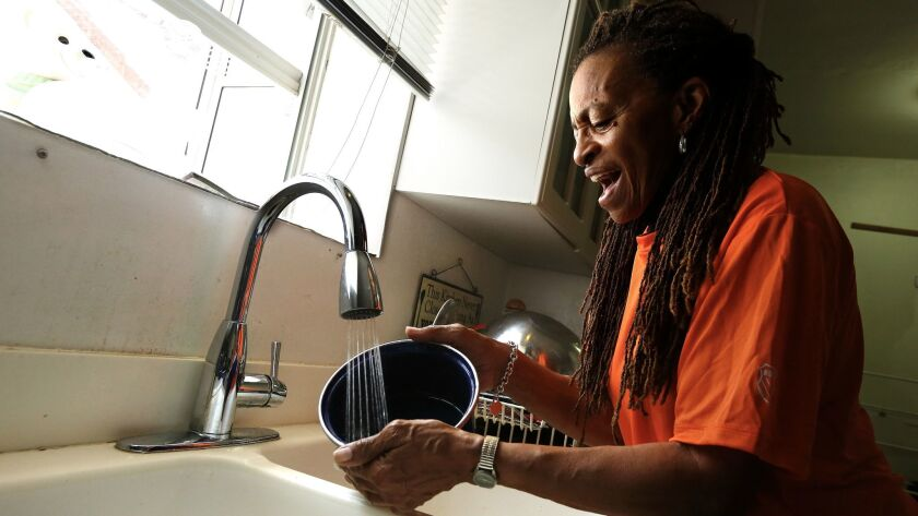 Doris Tillman, 71, washes pots and pans with running water — a luxury she was without for nine months after falling behind on an LADWP bill she disputed. She was able to make the required payment on the bill thanks to donations from readers who learned of her situation.