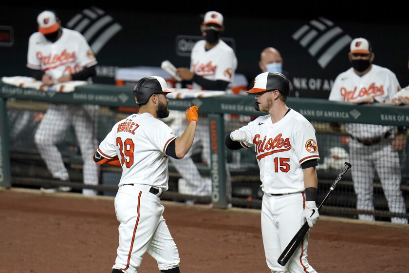 Baltimore Orioles' Renato Nunez, left, is greeted near the dugout by Chance Sisco after hitting a three-run home run off New York Mets starting pitcher Ariel Jurado during the first inning of a baseball game, Tuesday, Sept. 1, 2020, in Baltimore. Orioles' Cedric Mullins and Jose Iglesias scored on the home run. (AP Photo/Julio Cortez)