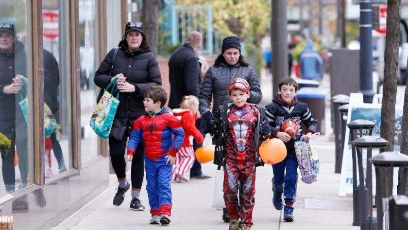 Friends and families roam downtown Evanston going from business to business trick-or-treating on October 28, 2017. A group is petitioning President Donald Trump to make Halloween always be the last Saturday of October.