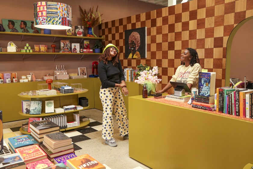 Two women talk in a store with books on display