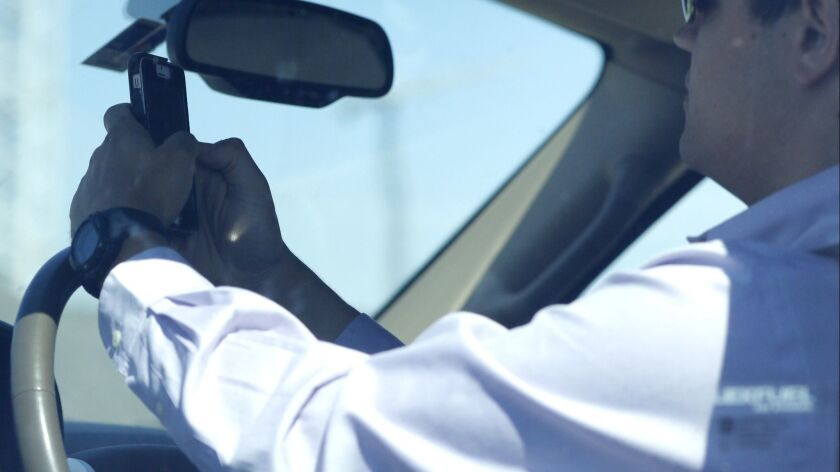 A man looks at his phone while driving on July 16, 2015, in Dallas, Texas.