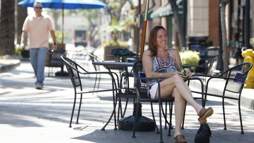 Mandy Abbott of Pasadena, sitting, enjoys Blue Grass music by the Fair Market Band, on the first day