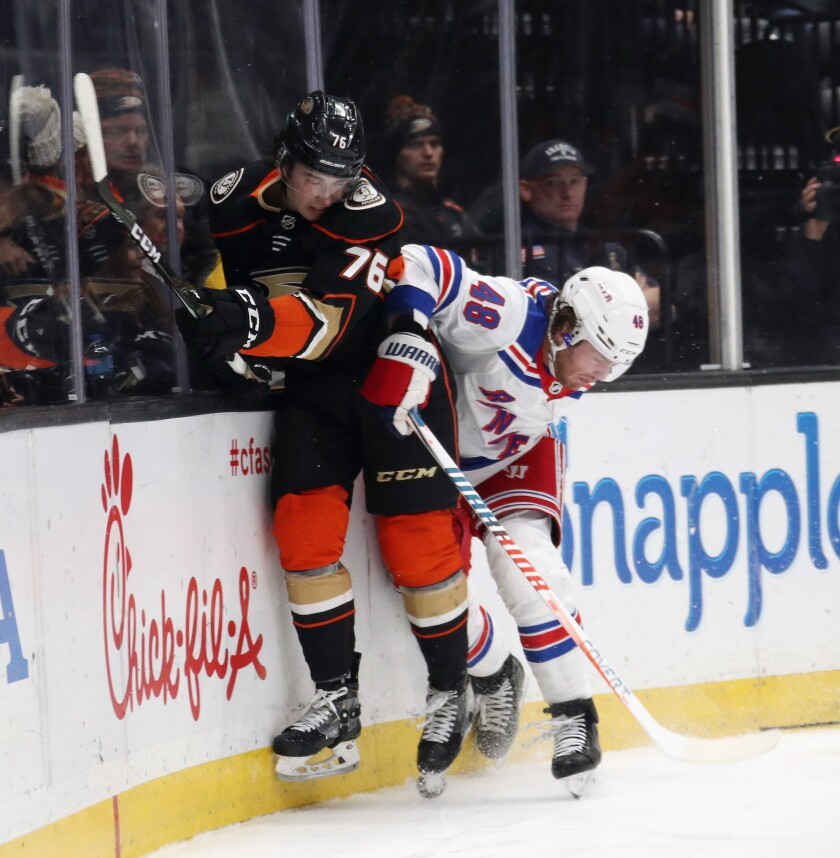 Ducks' Josh Mahura (76) is checked by New York Rangers' Brendan Lemieux (48) during the second period at the Honda Center on Saturday.