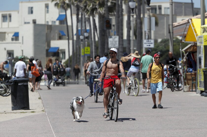 A bicyclist cruises as he walks his dog along the bike path on the north side of Huntington Beach Pier on Friday.