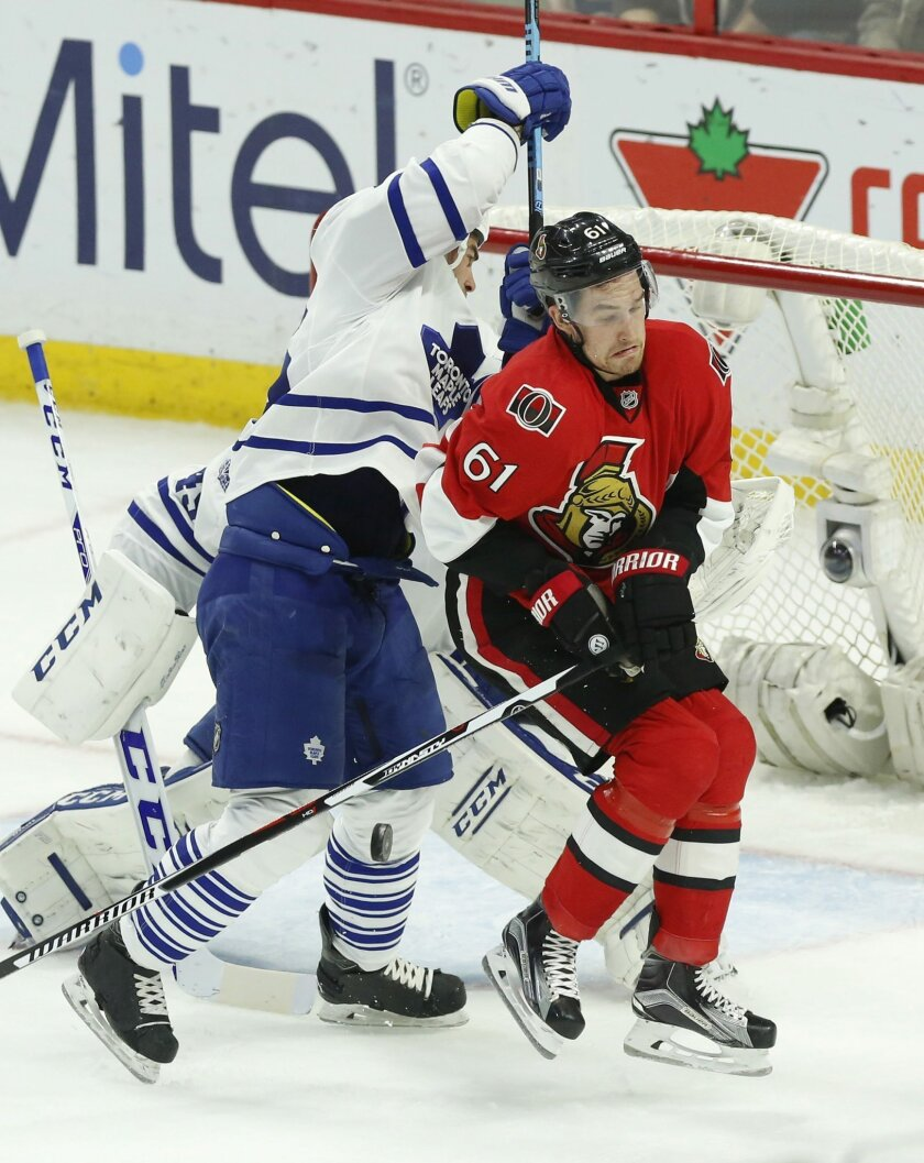 Ottawa Senators' Mark Stone (61) reacts after being hit by the puck as he screens Toronto Maple Leafs' goalie Jonathan Bernier (45) as teammate Roman Polak (46) reacts during the second period of an NHL hockey game, Saturday, Feb. 6, 2016, in Ottawa, Ontario. (Fred Chartrand/The Canadian Press via