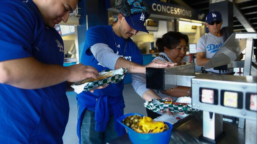 LOS ANGELES, CALIF. - MAY 27: Eric and Steve Soto put condiments on their Dodger Dogs at Dodger Stad