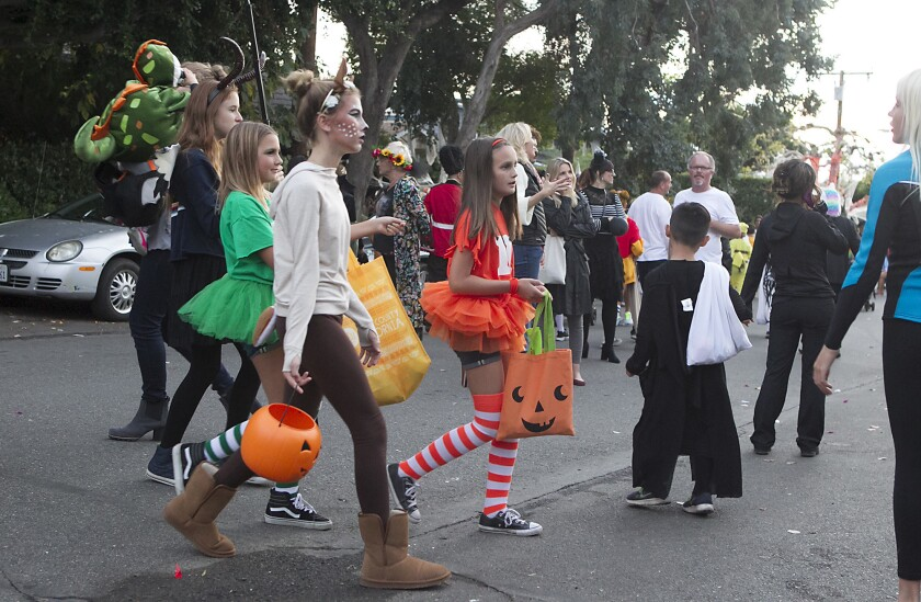 A group of girls in Halloween makeup and tutus joins a crowd at a Laguna Beach Halloween street party.