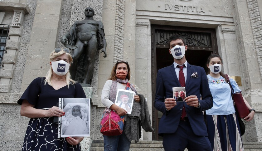 FILE - In this June 10, 2020 file photo, members of Noi Denunceremo (We will denounce) Facebook group, from left, Laura Capella, Nicoletta Bosica, Stefano Fusco and Arianna Dalba holds pictures of their relatives, victims of COVID-19, as they stand in front of Bergamo's court, Italy, Wednesday, June 10, 2020. Noi Denunceremo and affiliated non-profit committee are filing 100 new cases Monday, July 13, 2020, with Bergamo prosecutors, on top of 50 complaints lodged last month. (AP Photo/Antonio Calanni, file)