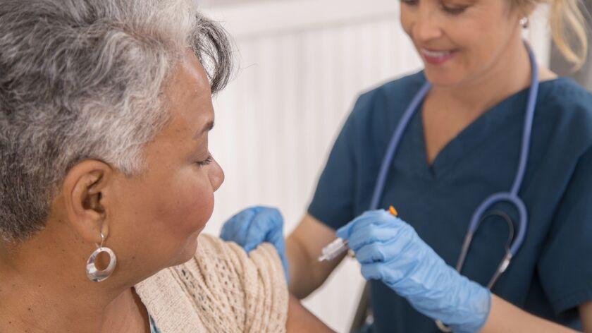 A nurse administers a flu shot to a patient.