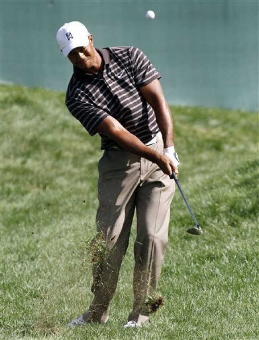Tiger Woods chips onto the 18th green in the third round of the Deutsche Bank Championship golf tournament at TPC Boston, Sunday, Sept. 5, 2010, in Norton, Mass. (AP Photo/Michael Dwyer)