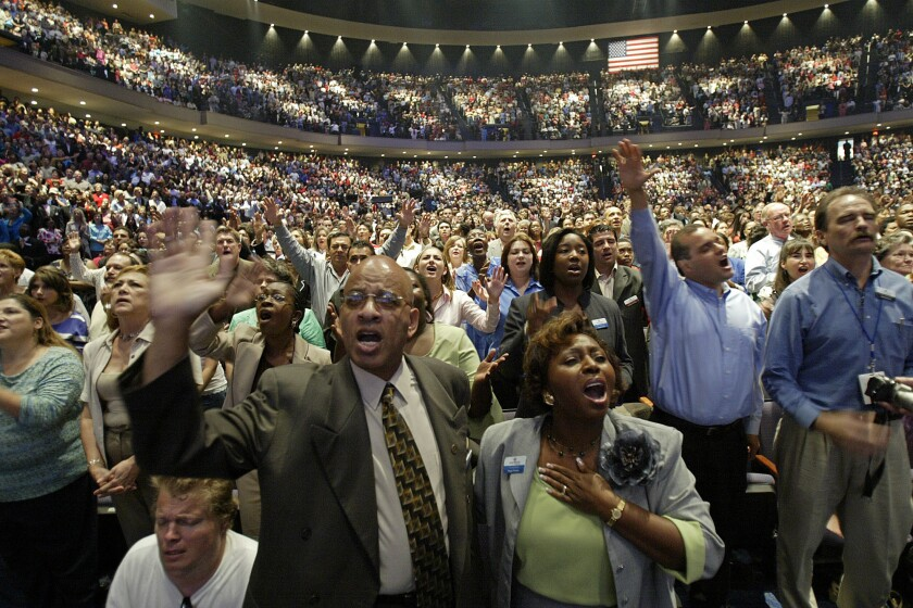 Members of the Lakewood Church worshiping at the event of a well-known televangelist and author.