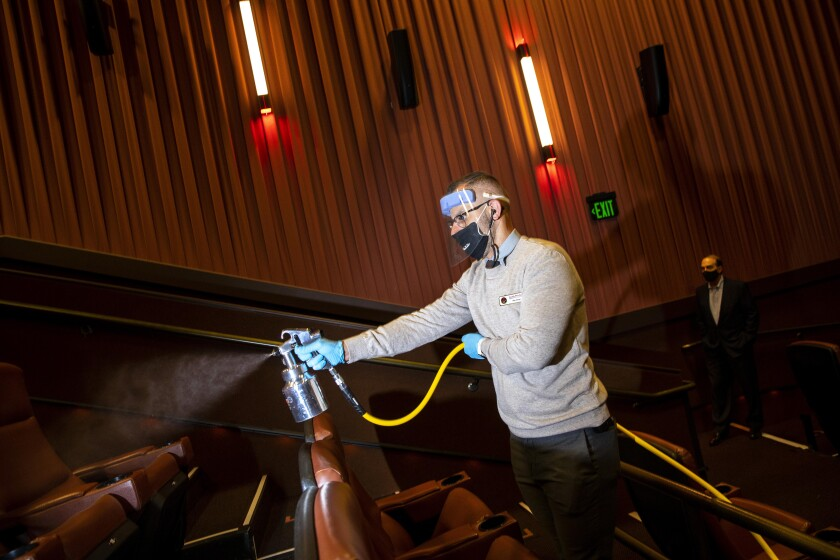 A worker sprays disinfectant in a theater.