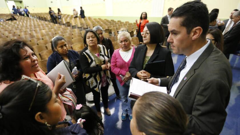 Antonio Plascencia, a la derecha, miembro del equipo de transición del LAUSD, escucha las preocupaciones de los padres de familia después de un foro con la superintendente Michelle King, realizado en Nightingale Middle School (Al Seib/Los Angeles Times).