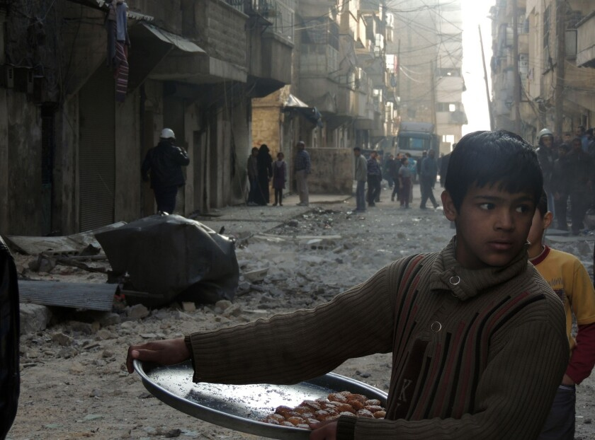 A Syrian boy sells sweets as civilians and emergency personnel inspect the damage in a street after government forces allegedly shelled the northern city of Aleppo.