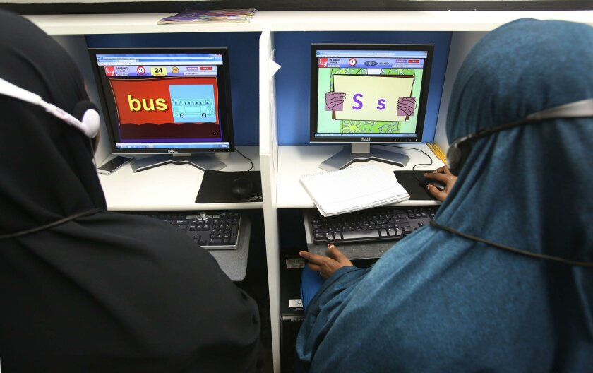Headphones and partitions between computers allow privacy and personalized learning for adults at elementary language levels.