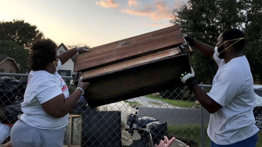 Maxine Williams and Steven Williams toss out a waterlogged hope chest damaged beyond repair in Port Arthur. The city was flooded after Hurricane Harvey struck the Gulf Coast.
