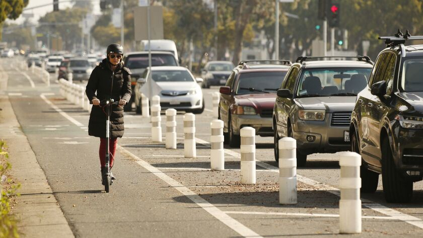 A scooter rider navigates the bike lane along Venice Boulevard in Mar Vista, Calif. on March 5.