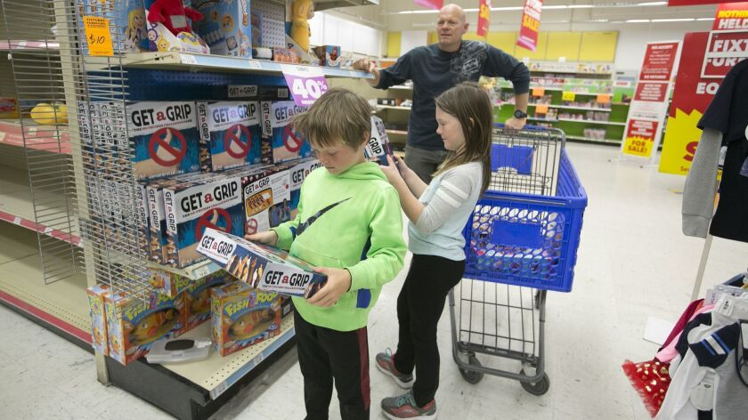 Sebastian Bencke, 7, and his sister Danica, 9, look over several discounted toys as their father Jake takes in the Morena outlet of Toys 'R' Us. The retail giant is shuttering stores nationwide.