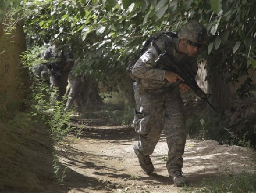 FILE - In this May 8, 2010 file photo, U.S. Army Pfc. James Lifsey ducks as he walks under tree cover while on a foot patrol with 2nd Platoon, Alpha Company, 2nd Battalion, 1st Infantry Regiment of the 5th Stryker Brigade, in Afghanistan's Kandahar province. (AP Photo/Julie Jacobson, File)