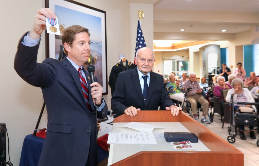 U.S. Congressman Mike Levin holds one of the many medals he's presenting to 99 year World War II veteran George Coburn, at right, for his duty during the war here at Fairwinds Ivey Ranch retirement community where George lives.