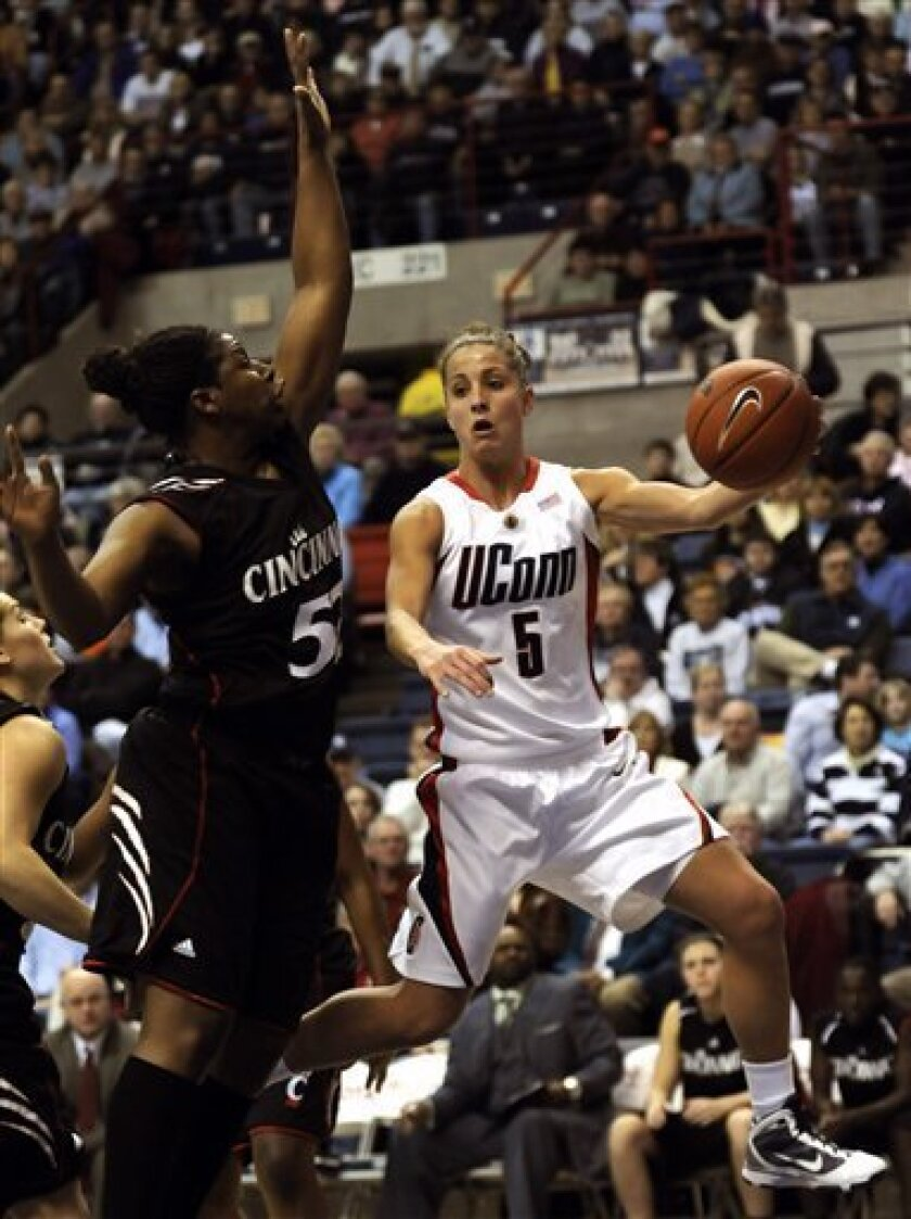 Connecticut's Caroline Doty (5) passes the ball as Cincinnati's Michelle Jones guards her in the first half of an NCAA women's college basketball game at Storrs, Conn., Thursday, Jan. 7, 2010. (AP Photo/Bob Child)