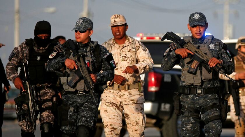 Members of the Mexican federal police and the Mexican army stand guard at the scene of a shooting in Tijuana on April 25.