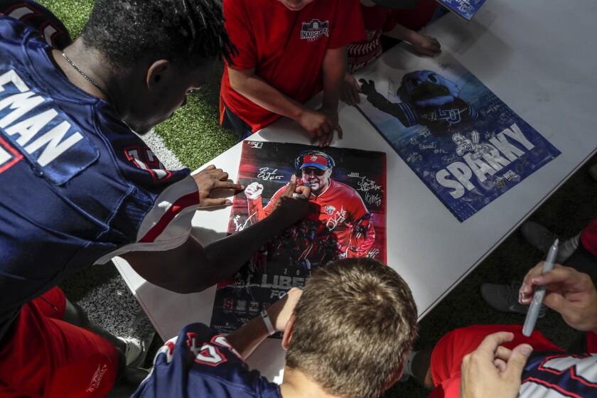 Liberty football players autograph a poster of head coach Hugh Freeze during a fan appreciation event.