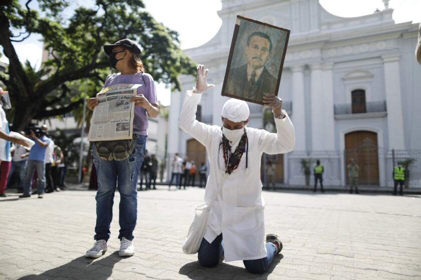 Yeni Vasquez raises a portrait of the late, Venezuelan Dr. Jose Gregorio Hernandez