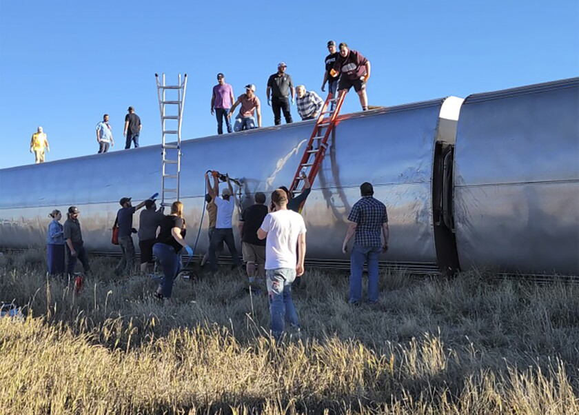 People work at the scene of an Amtrak train derailment.