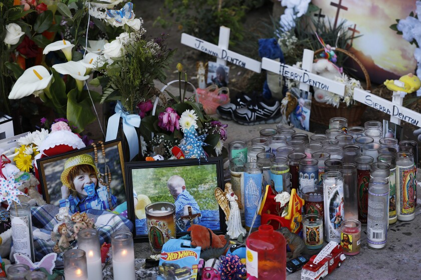 Photos, flowers, trinkets and candles in front of three small wooden crosses at a sidewalk memorial