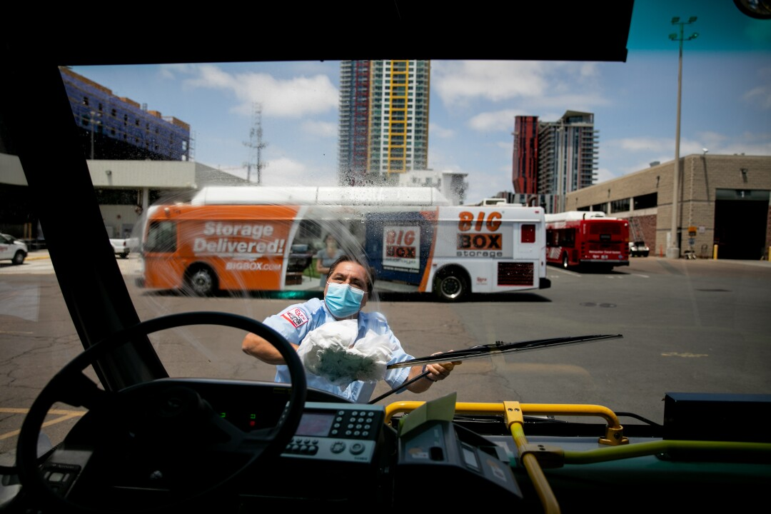 Christopher Castor, 56, who pilots the number 7 bus that traverses University Avenue, cleans his windshield.
